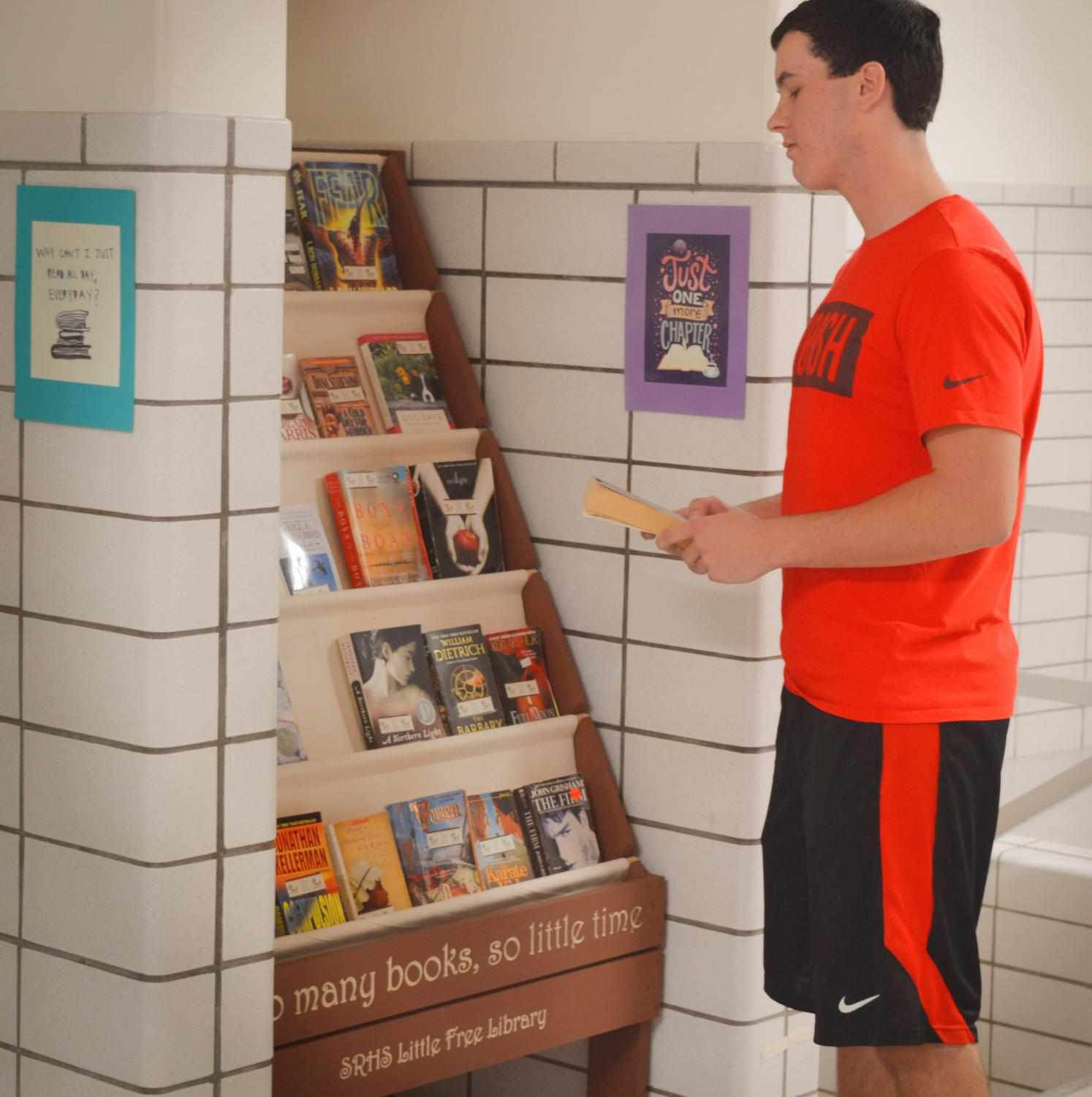 Junior Logan Croll takes advantage of the books in the new free library created by Mrs. Elford.