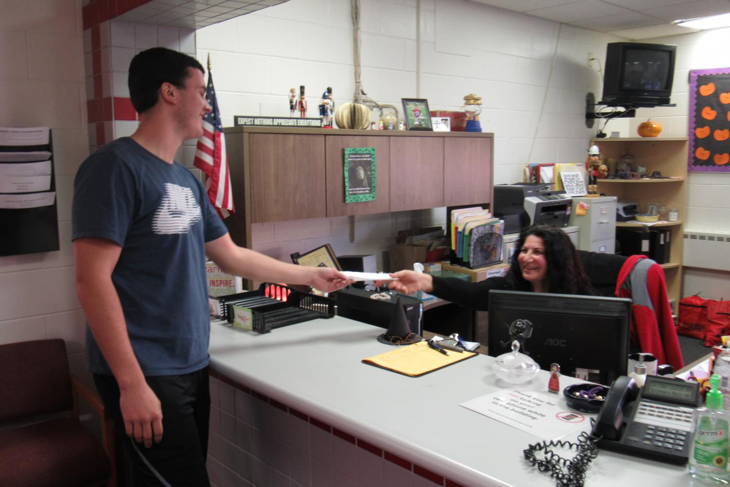 Junior Logan Croll turns in an excuse to Mrs. Marini in the high school office.