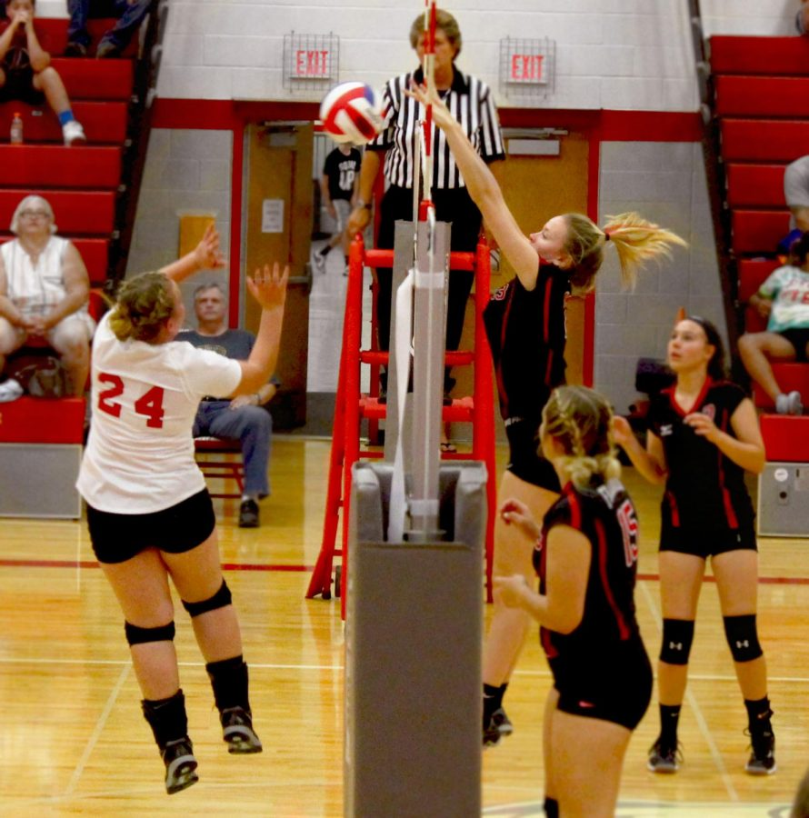 Junior+Morgan+Malinski+jumps+up+from+the+side+to+block+the+opposing+team+from+scoring.