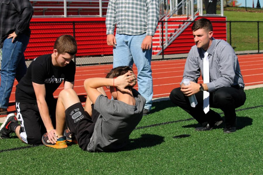 Tyler Hinkle spots Kyle Errera doing sit-ups as Mr. Miller advises during a meeting of the Military Education Club.