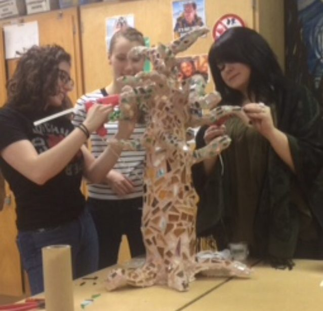 Ms. Pauletich helps seniors Ava Marini and Barbie Cessar with a tree sculpture.