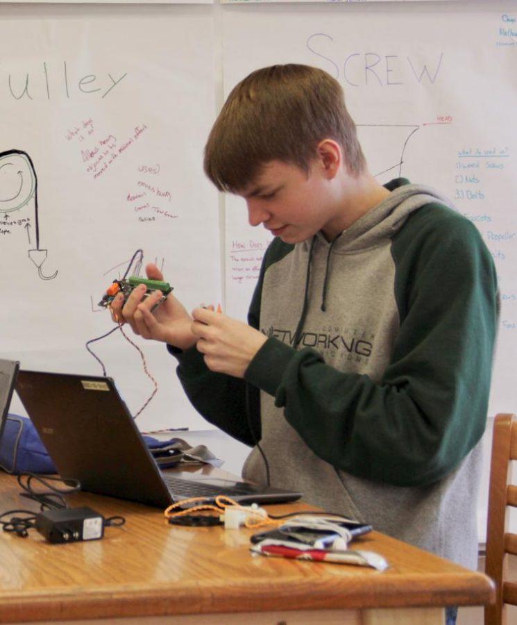 Shane Schettler designs a robot.