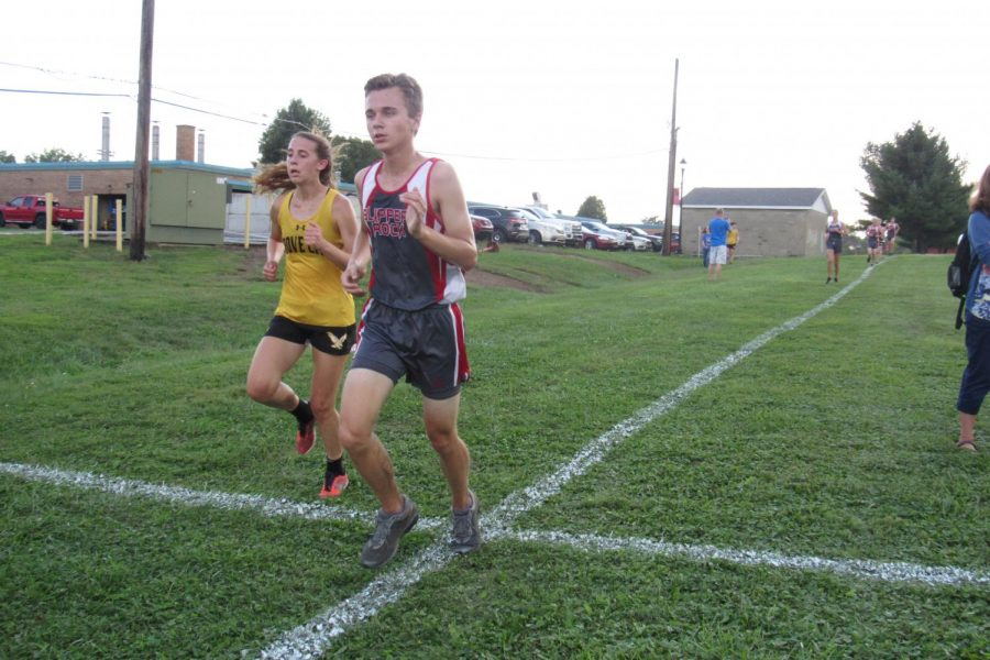 Go+For+it%21+Sophomore+Garrett+Galcik+pushes+ahead+of+a+rival+on+the+final+home+meet+of+the+season.+Slippery+Rock+ran+against+Grove+City+on+September+19th.+%22I+just+kept+thinking%2C+we%27re+almost+there%2C%22+Galcik+said.+Photo+by+Nolan+Holtz.