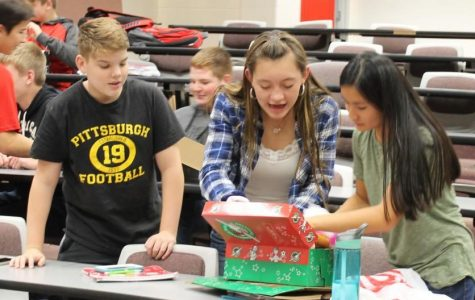 Shoebox Stuffers Freshman Tanner Kennedy, sophomore Lauren Pflueger, and sophomore Qin Raisley stuff their shoebox to the brim with toys that will be going to some lucky child in a third-world country. Pflueger said that she enjoyed the project because she loves putting smiles on other people's faces and knowing that a kid who doesn't have much got to open her box makes her happy, too.