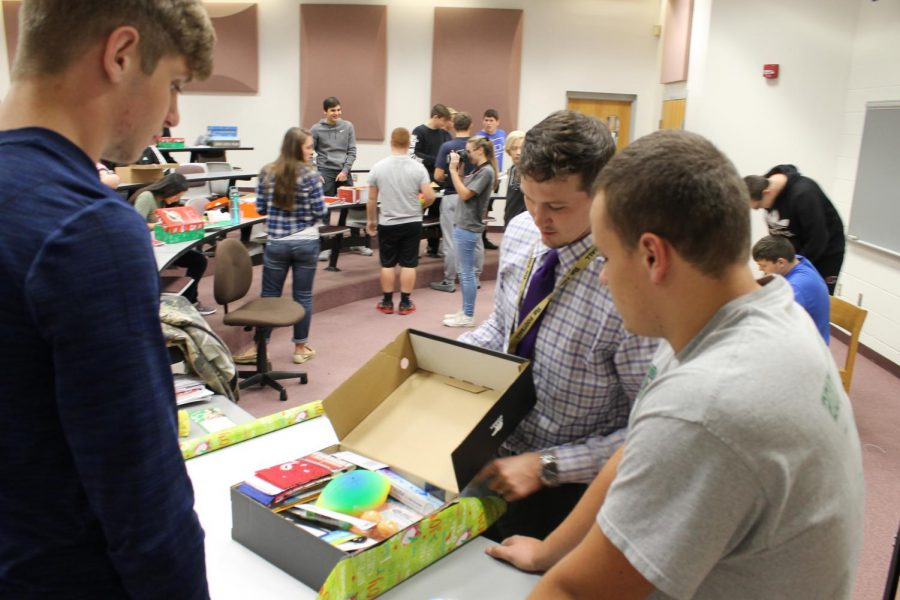 Topping It Off Mr. Christy helps senior Ryan Broad and sophomore Shayne Gumpp put the finishing touches on their shoebox. Broad said working with a group enhanced the experience because they were able to get a lot more done and have fun while doing it.