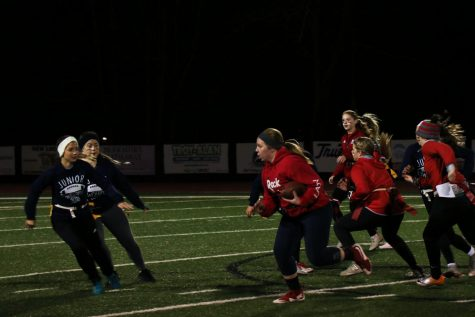 Head to head. The seniors attempt to drive the ball up the field, while the juniors try to thwart their plans.  The Powderpuff game occurred on November 8th. Photo by Devin Eakin.